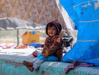 Una niña desplazada afgana sonríe bajo las lonas de la tienda en la que vive temporalmente en un parque de Kabul.