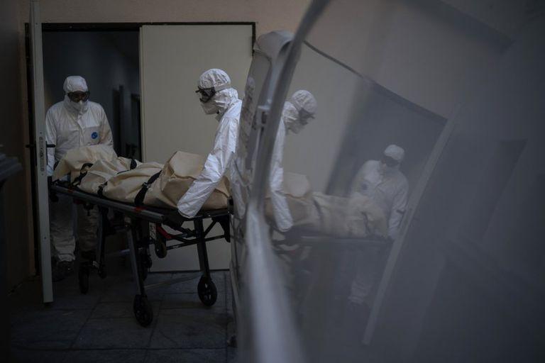 Dos empleados de una funeraria retiran el cuerpo de una víctima de covid de una residencia de ancianos, en Barcelona.