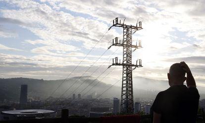 Una persona observa el cableado con el que Red Eléctrica transporta energía sobre la ciudad de Bilbao.
