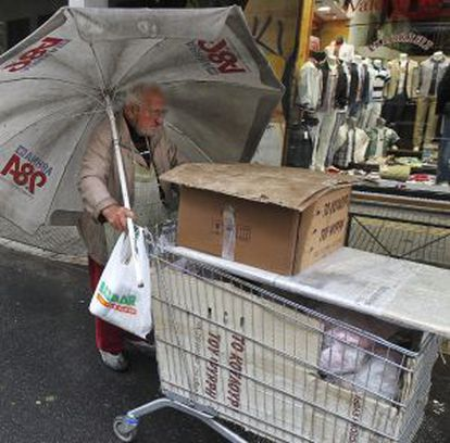 Un vendedor callejero empuja su carrito bajo la lluvia en Atenas.