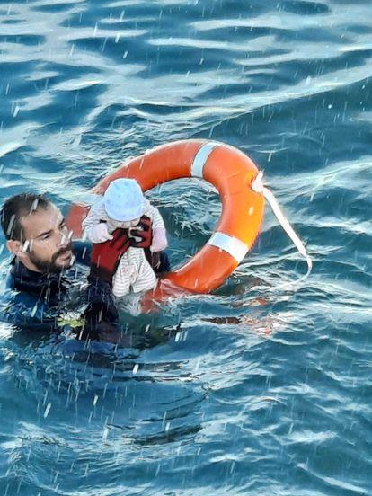 Un submarinista de la Guardia Civil, con un bebé cuya familia se había echado al agua en Ceuta, este lunes.