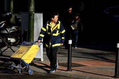 Una cartera de Correos con el carrito en la zona de Argüelles, Madrid.