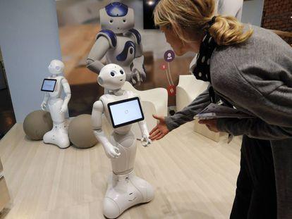 Una mujer saluda al robot Pepper durante una feria tecnológica en París.