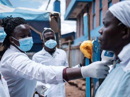 Tres trabajadores voluntarios toman la temperatura a una habitante del barrio de chabolas de Kibera, en Kenia.