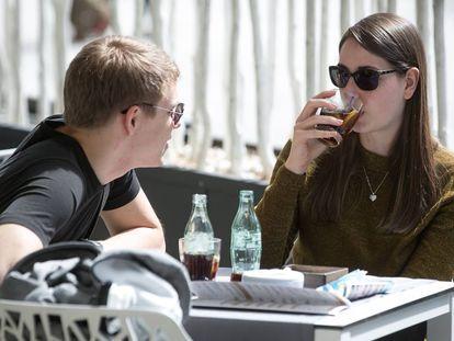 Dos jóvenes toman unos refrescos en una terraza en Barcelona
