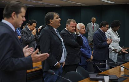 Un grupo de diputados brasileños reza en una sesión parlamentaria celebrada en su sede en Brasilia.