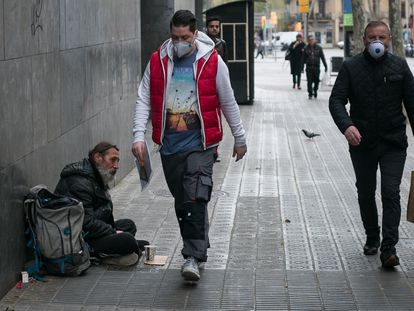 Dos hombres con mascarilla sanitaria pasan por delante de otro que pide limosna en la calle.