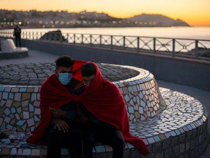 Dos jóvenes inmigrantes se protegen del frío a primera hora de la mañana cerca de la playa ceutí de El Tarajal.