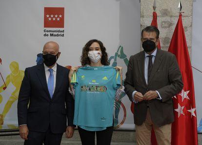 La presidenta de la Comunidad de Madrid, Isabel Díaz Ayuso, posa con una camiseta durante el acto por el que recibe el título de Maratoniana de Honor por parte de la Asociación Deportiva Maratón Popular de Madrid.