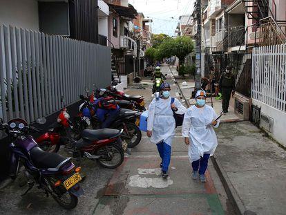 Dos trabajadores de la salud caminan con la vacuna del laboratorio chino Sinovac, en un barrio de Cali, Colombia, el 18 de marzo pasado.