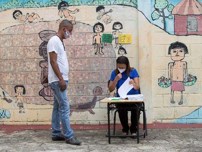 Un hombre acude a buscar un kit escolar en una escuela en Santo Domingo, República Dominicana, este lunes.