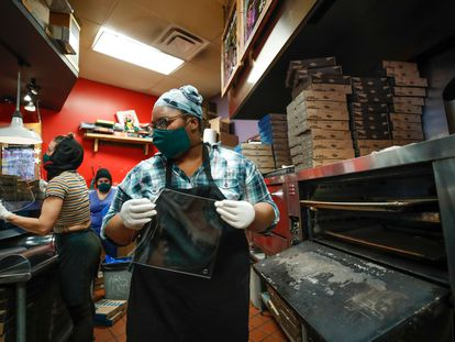 Empleadas de la pizzeria Dimo's fabrican mascarillas de acrílico en Chicago.