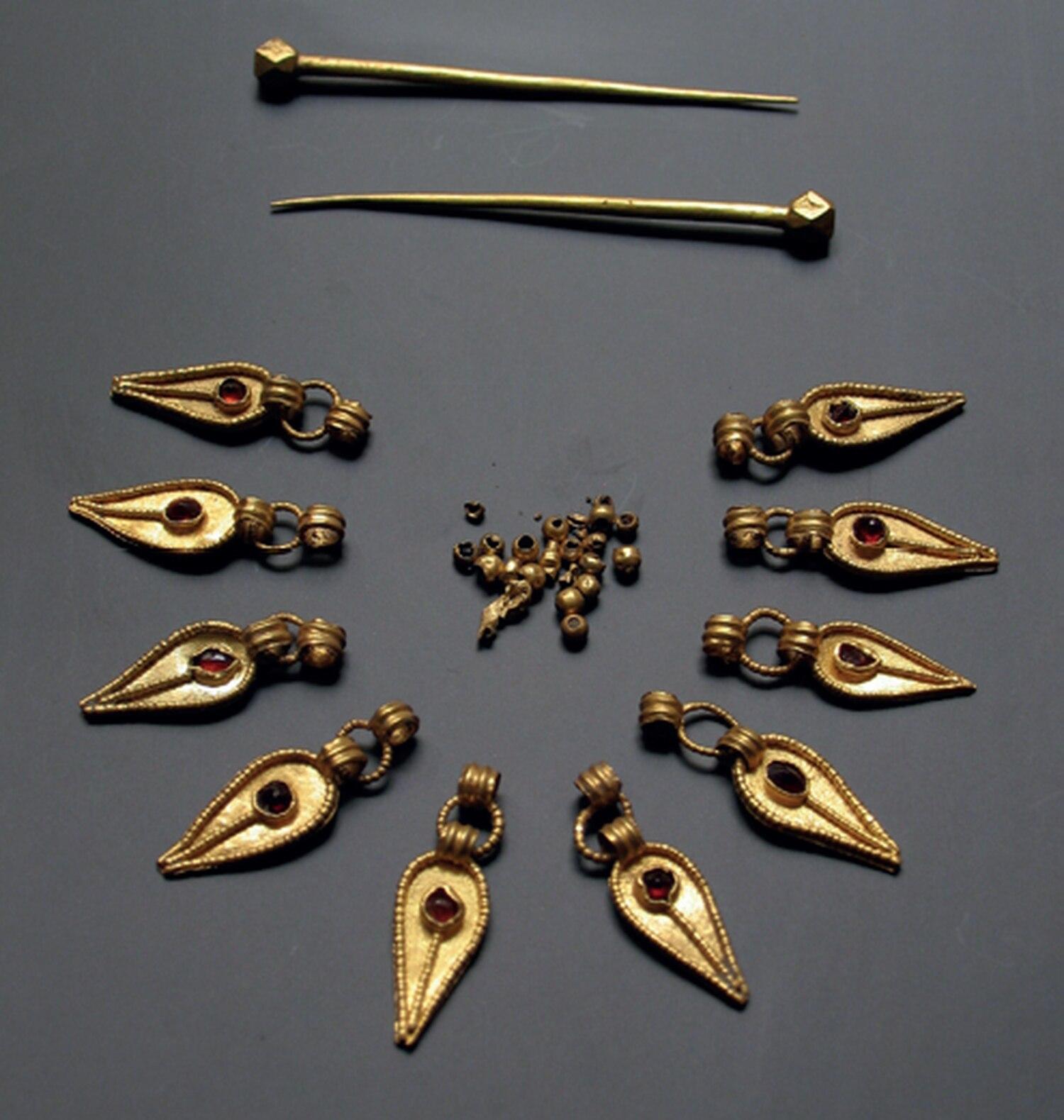 Piezas de uno de los collares y alfileres de oro que llevaba una joven sueva hallada en Mérida.