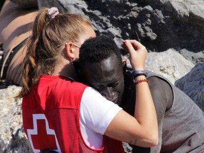 Una trabajadora de la Cruz Roja y un migrante que ha logrado cruzar uno de los espigones fronterizos de Ceuta este martes se abrazan. Ceuta ha vivido hoy una avalancha de migrantes sin precedentes en España al registrarse la entrada en poco más de 24 horas de unas 8.000 personas, muchas de ellas menores. EFE/Reduan