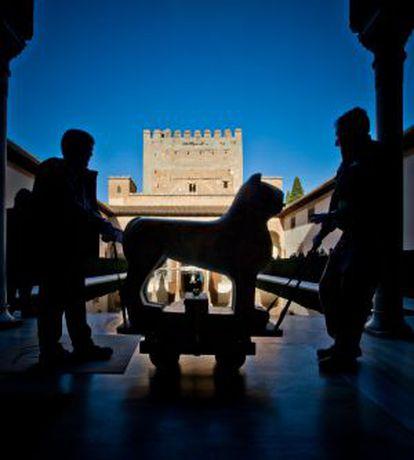 Dos operarios trasladan por el patio de Comares a uno de los leones restaurados.
