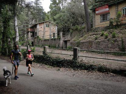 Dos personas pasean con un perro junto al antiguo poblado de Camarasa