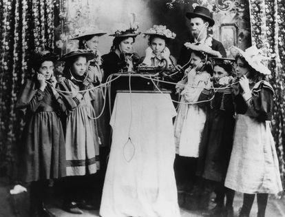 Un grupo de personas prueba una primitiva gramola en Salina, Kansas (c. 1895)