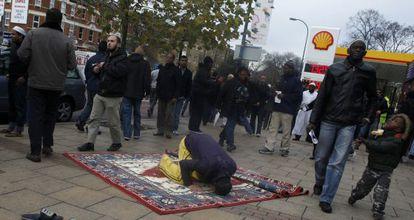 Un musulmán reza en la acera de una calle de Londres, en el exterior de una mezquita, en 2011