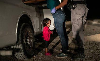 Una niña hondureña llora mientras su madre es registrada por un policía estadounidense de fronteras en Texas, en 2019.
