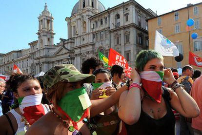 Pañuelos con los colores de la bandera italiana cubren los rostros de varios manifestantes en Roma.
