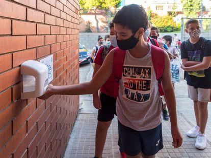 Un alumno se pone gel hidroalcohólico en la escuela rafael Casnova de Badalona antes de entrar en el centro.