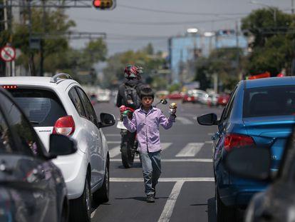 Un niño realiza malabares entre las filas de vehículos el 10 de junio de 2020, en Ciudad de México (México). En América Latina, la covid-19 ha incrementado el trabajo infantil.