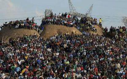 Familiares y miembros del asentamiento improvisado de Wonderkop en las colinas del lugar donde sucedió la masacre para oficiar un servicio religioso en honor a los mineros de la empresa Lonmin, que fueron abatidos por la Policía sudafricana en el campamento minero de Marikana. EFE/Archivo