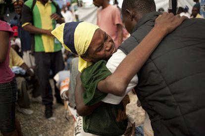 Un hombre ayuda a un enfermo de cólera en el hospital de Saint Marc, en Haití.