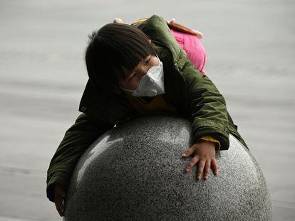 Un niño con mascarilla juega en la estación de tren de la ciudad china de Changsha.