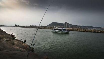 Un catamarán turístico saliendo por la desembocadura del Júcar en Cullera.