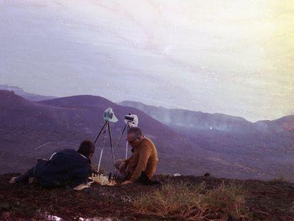 Dos hombres con cámaras sobre trípodes juegan al ajedrez tras la erupción del volcán Teneguía en la isla de La Palma en 1971.