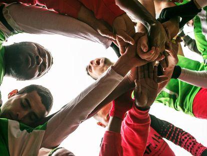 Los jugadores de Alma de África buscan concentrarse agarrándose las manos antes del partido contra Alcalá del Valle (Cádiz) el pasado 19 de febrero. Alma de África es un equipo de fútbol de Jerez de la Frontera compuesto por inmigrantes, en su gran mayoría africanos, que juega en 3ª división andaluza.