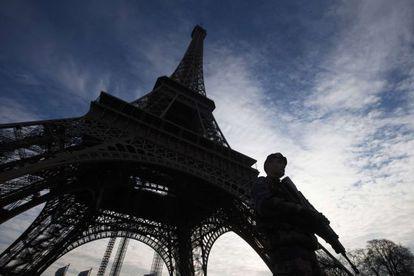 Un soldado vigila la torre Eiffel en París, resguardada por las amenazas de los grupos terroristas contra objetivos franceses.