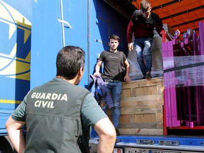Dos polizones de origen albanés se bajan del remolque en el que intentaban viajar al Reino Unido.
