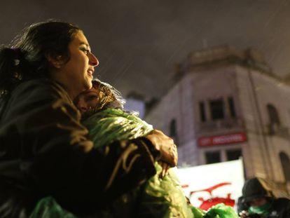 Dos jóvenes favorables al aborto legal se abrazan y lloran bajo la lluvia frente al Congreso argentino.