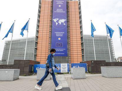 Una mujer camina frente a la sede de la Comisión Europea.