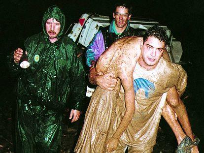 Miembros de un equipo de rescate trasladan a una de las víctimas de las inundaciones del camping de Biescas (Huesca).