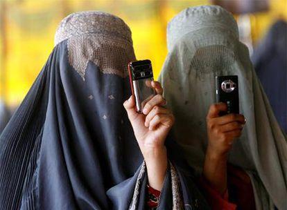 Dos mujeres ataviadas con el <i>burka</i> hacen fotos con sus móviles durante un mitin de Hamid Karzai en Kandahar. Mujeres afganas se disponen a votar el 20 de agosto pasado.