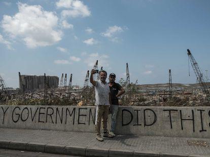 """Los libaneses acuden a hacerse un 'selfie' frente a los restos calcinados del puerto de Beirut donde se lee en una pintada: """"Mi Gobierno hizo esto""""."""