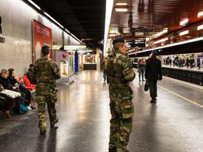 Varios militares patrullan en la estación de metro de Auber, en París.