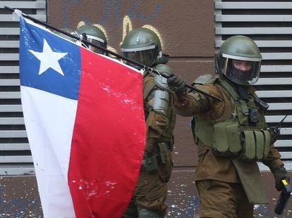 """Un policía enarbola una bandera chilena en la Plaza Italia de Santiago (Chile), rebautizada popularmente como """"Plaza Dignidad"""", el pasado 20 de octubre."""