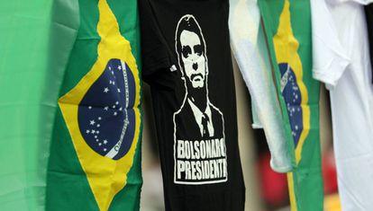 Camiseta de Bolsonaro al lado de banderas de Brasil.