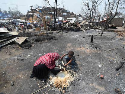 Una madre y su hijo intentaban rescatar arroz tras el incendio, el pasado jueves en el campo de refugiados de Kutupalong (Bangladés).