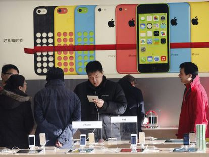 Varios clientes revisan dispositivos en una tienda de Apple en Pekín.