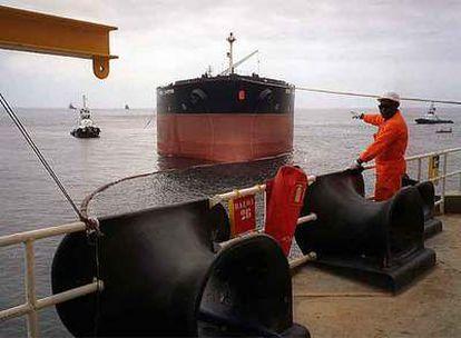 Un operario de Total señala hacia un buque de carga español en la plataforma petrolífera Girassol, en la costa angoleña.