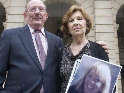 Los padres de Laura Cerna, con una foto de su hija en la puerta de los juzgados de Sevilla.