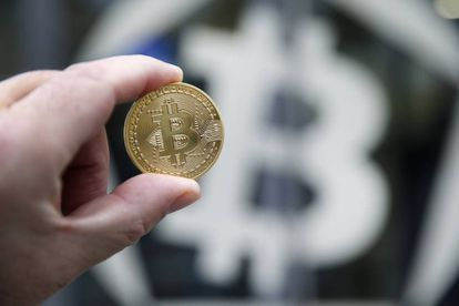 Una moneda de bitcoin sobre el símbolo de la criptodivisa