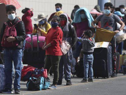 Un grupo de personas con mascarillas, en una parada de autobuses en Lima (Perú).