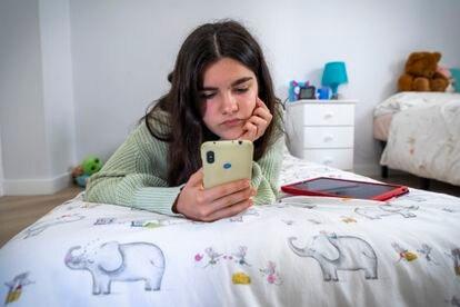 Una adolescente durante el confinamiento trastea con el móvil en su habitación.
