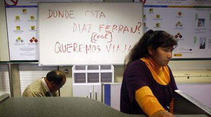 Pasajeros afectados por el cierre de Air Comet, ayer en el aeropuerto de Barajas (Madrid). Detrás, un cartel contra Díaz Ferrán.